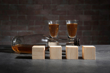 Alcohol and wooden cubes on table