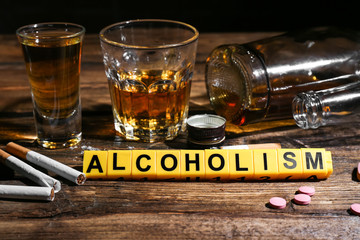 "Composition with word ""Alcoholism"", cigarettes and drugs on table"