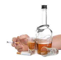 Man in handcuffs holding cigarette near bottle of alcohol on white background