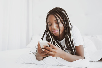 A beautiful African woman lies on her stomach, on the bed and looks into the phone. Check social networks, send sms. The girl is wearing a T-shirt, pigtails on her head. Portrait.