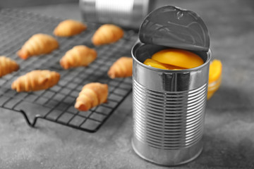 Can with pickled apricots on table
