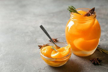 Jar and bowl with pickled apricots on table