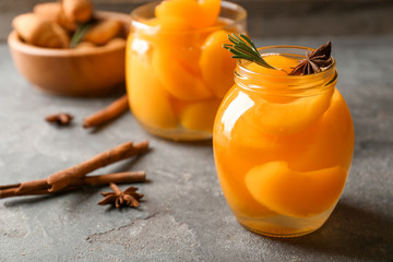 Jar with pickled apricots on table