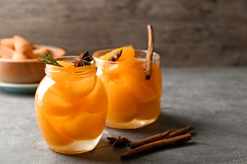 Jars with pickled apricots on table