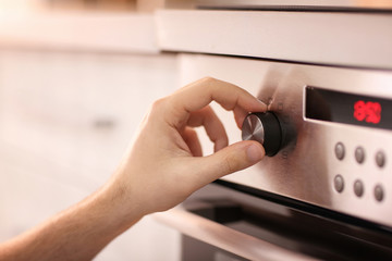 Man adjusting electric oven in kitchen, closeup