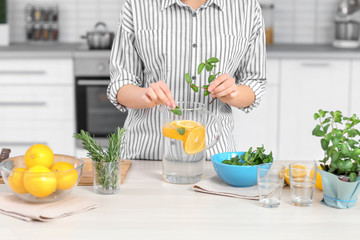Young woman preparing tasty lemonade in kitchen