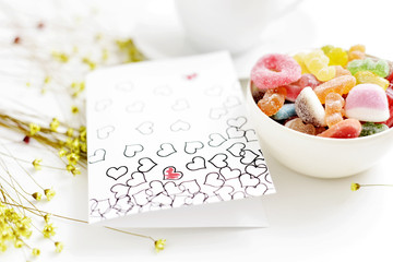 homemade postcard with some hearts on a table