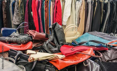 64e71c65b9c62 Verkauf secondhand Handtaschen auf dem Wühltisch und gebrauchte Kleider im  Kleiderständer - Sale secondhand handbags on