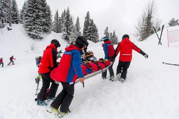 Kameraden der Bergwacht versorgen eine gestürzte und verletzte Skifahrerin