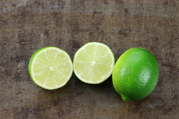 lime fruit and a cut one on a grunge background