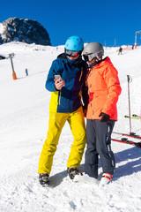 Junges Pärchen mit Smartphone auf der Skipiste