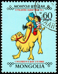 Ukraine - circa 2018: A postage stamp printed in Mongolia shows Children, a boy and a girl ride on a smiling camel. Series: Day of the child. Circa 1966.
