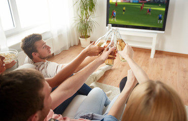 friends clinking beer and watching soccer game
