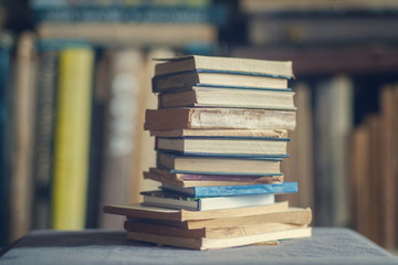 A stack of dusty shabby books in front of blurry shelves