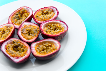 Passion fruit on a white plate on blue napkin Outdoor background