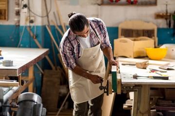 Carpenter working on wooden plank in workbench