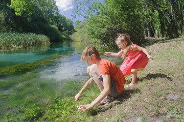 Girl and boy siblings playing near water of Italian Tirino river in Abruzzo