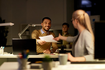 coworkers with papers working late at office