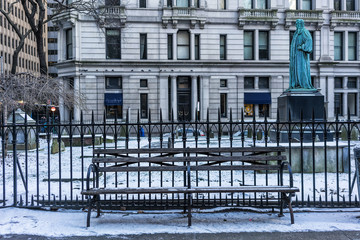 Wooden bench in New York City with snow.