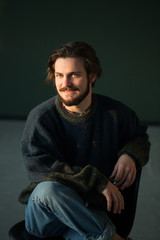 Portrait of hadsome young bearded stylish man sitting on the chair in studio