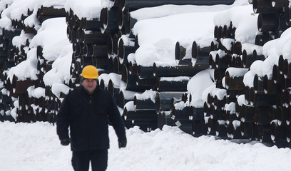 An employee walks past a stack of steel round pipes at the Ariel Metal steel trader warehouse in Podolsk