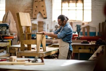 Carpenter examining a wooden chair