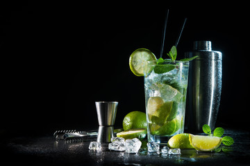 Mojito cocktail with fresh mint, lime, ice cubes and bar shaker