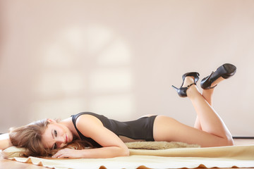 Girl is lying on the bed.