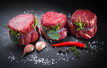 Raw beef fillet steaks mignon on dark background