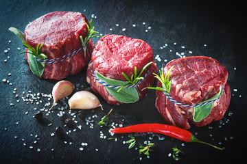 Raw beef fillet steaks mignon on dark background