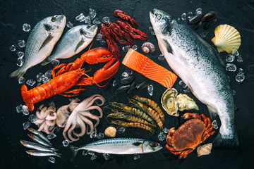 Foto op Canvas Vis Fresh fish and seafood arrangement on black stone