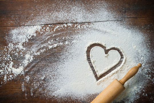 Baking background with the rolling pin, heart shape and flour on the wooden table