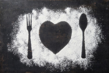 Spoon, Fork and plate in heart shape, flour sprinkled around the dark board