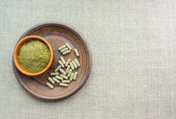 Supplement kratom green capsules and powder on brown plate. Herbal product alt-medicine kratom is  opioid. Home alternative pain remedy, opioid addiction, dangerous painkiller, overdose