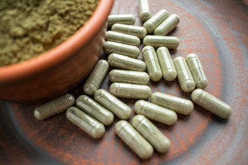 Supplement kratom green capsules and powder on brown plate. Herbal product alt-medicine kratom is  opioid. Home alternative pain remedy, opioid addiction, painkiller, overdose. Selective focus