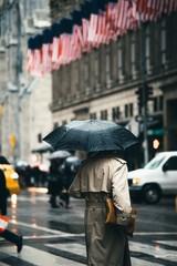 Woman walking with umbrella on street during rain