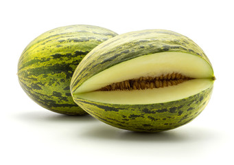 Two melons Piel de Sapo (Santa Claus Christmas variety) one cut open isolated on white background green striped outer rind.