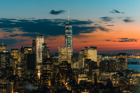 View of modern cityscape with One World Trade Center at dusk