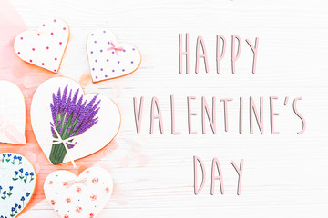 happy valentine's day text sign flat lay. pink cookie hearts and flowers confetti on white rustic wooden background. space for text. greeting card concept. valentines bright image