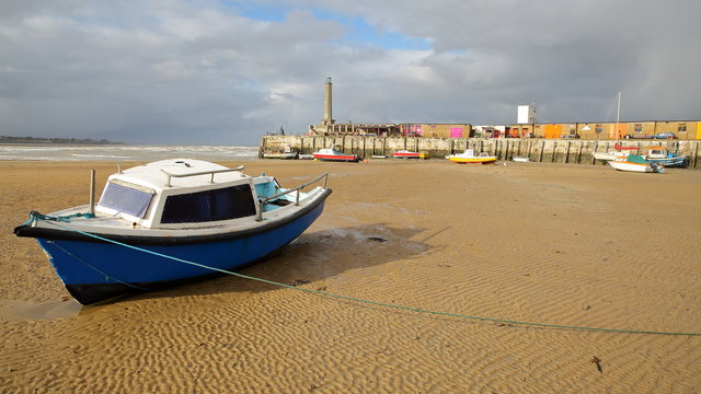 The beach at low tide with mooring boats and Margate Harbor Arm in the background, Margate, Kent, UK