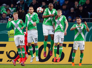 Players of Wolfsburg jump during a free kick of Freiburg during their quarter-final German Cup (DFB-Pokal) soccer match in Wolfsburg