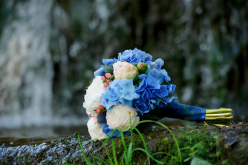 White and blue flowers wedding bouquet on a waterfall background