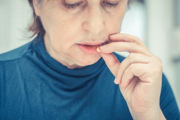 Close up of sad mature woman taking a medicine.