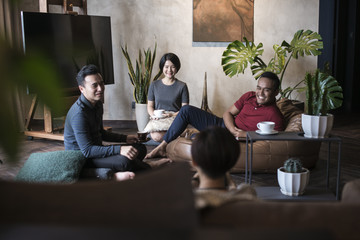 Group of friends talking and having fun together in the living room.