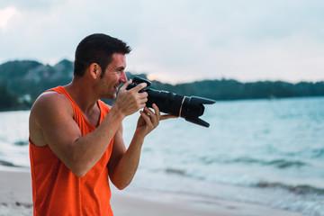 Cheerful photographer on beach