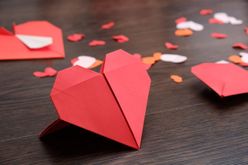 Valentine's Day background with origami paper hearts on wood backdrop.