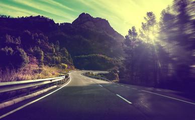 Concepto de viajes por carretera.Carretera de montaña con curvas y puesta de sol.Seguridad y precaución conduciendo.