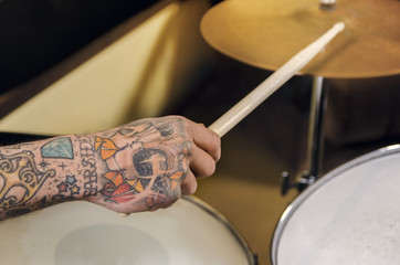 Closeup tattooed arm playing drums
