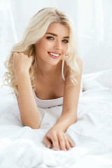 Beautiful Happy Woman On Bed In Light Interior