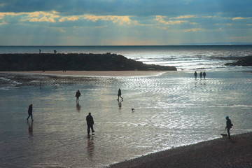 Silhouettes of people walk on the wet sandy beach during low tide in Sidmouth, Devon